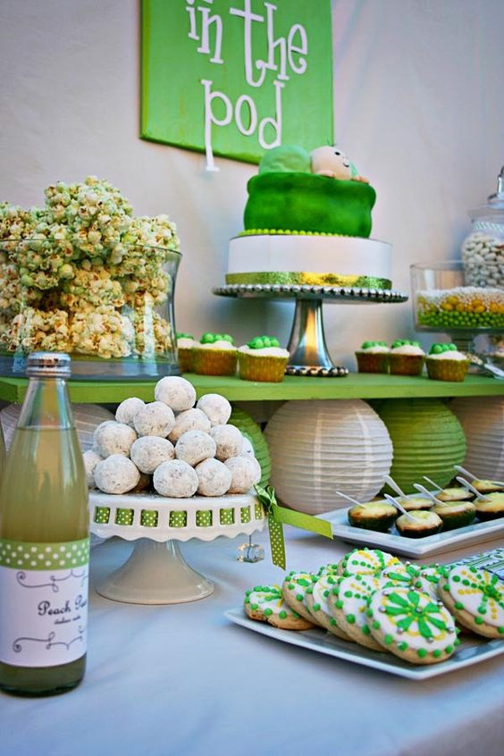 a green and white dessert table with various stands, trays and a sign over it