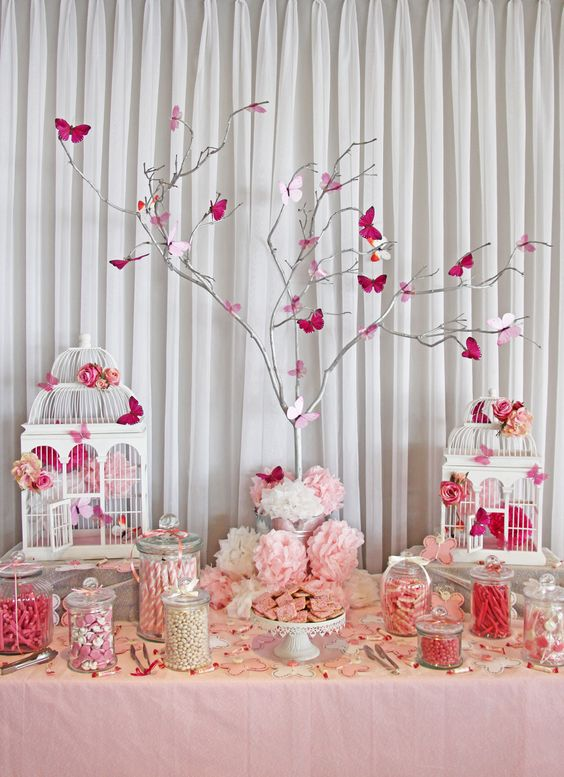 a pink and white baby shower table with vintage cages, a whitewashed tree with pink butterflies, vintage stands with various sweets