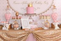 a bright pink and gold dessert table with a letter backdrop, a gold sequin tablecloth, refined stands and bowls