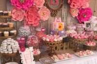 a bright pink and fuchsia dessert table with large paper flowers, touches of brass, monograms and letters