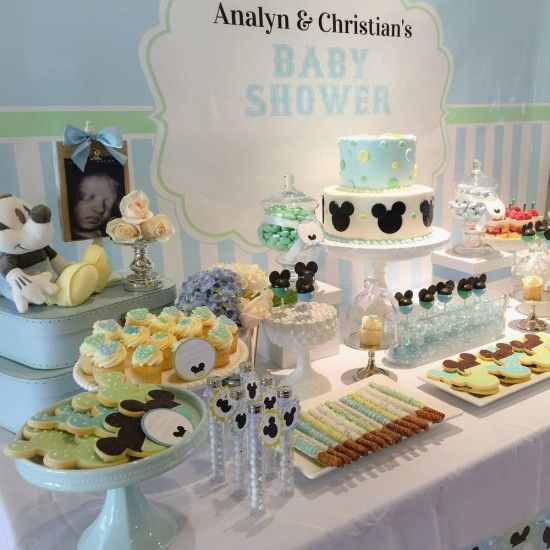 a gender neutral baby shower dessert table done in blue and green, with lots of Mickey Mouse desserts and decorations