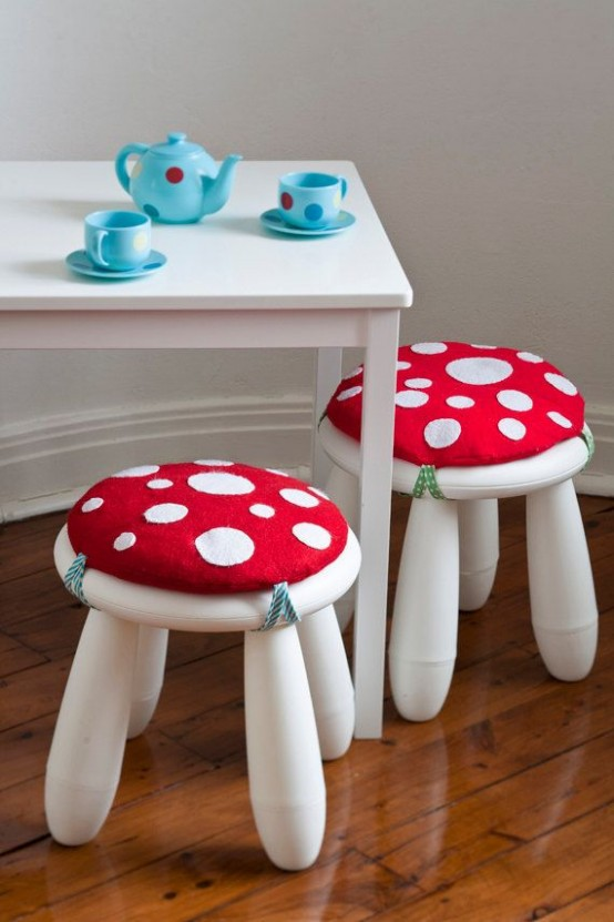 a white table and white IKEA Mammut stools spruced up with bright mushroom-inspired pillows to look whimsy
