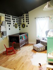 a boho black and white nursery with a dark IKEA Sundvik crib, a colorful tassel garland and a boho ottoman