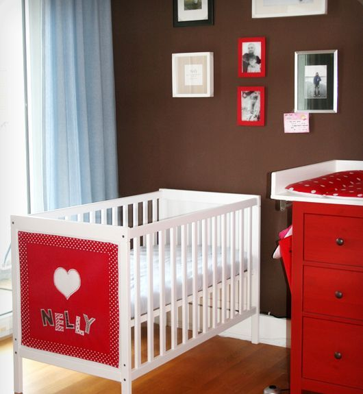 a bright chocolate brown, red and white nursery with a white IKEA Sundvik crib and a red accent on it for more fun