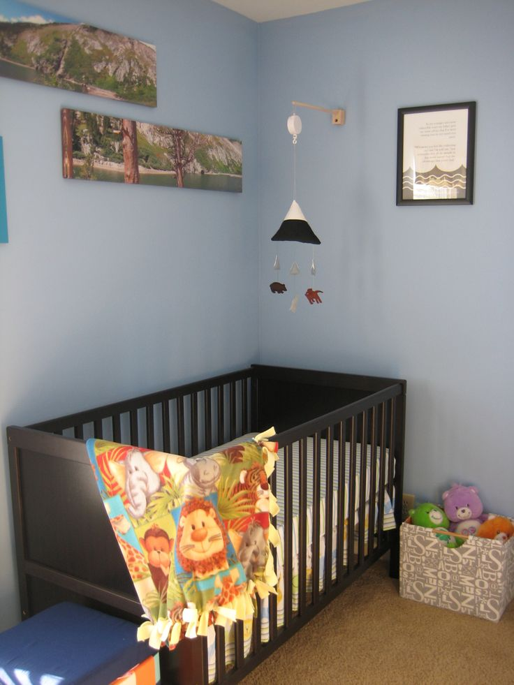 a pastel nursery with blue walls and a neutral floor plus a dark stained IKEA Sundvik crib that makes a statement