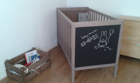 a neutral IKEA Sundvik crib is spruced up with a chalkboard side for some interactivity and creativity