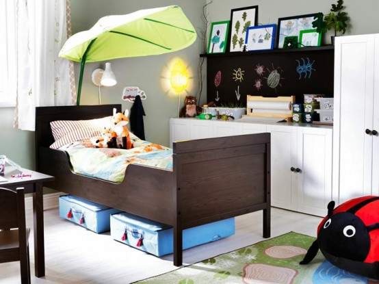 a bold nursery with a chalkboard, white furniture, a dark Sundvik bed, colorful frames, lanterns and fun toys