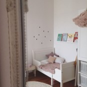 a dreamy nursery in white and dusty pink, with an IKEA Sundvik bed, shelves and vintage furniture
