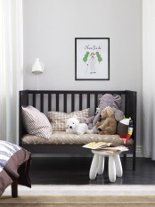 a monochromatic nursery with a dark IKEA Sundvik crib, dark furniture and floors and all neutral everything