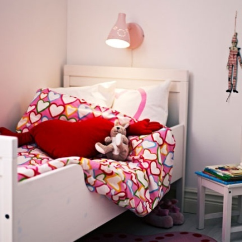 a small and cozy nursery with an IKEA Sundvik bed and colorful bedding and lamps