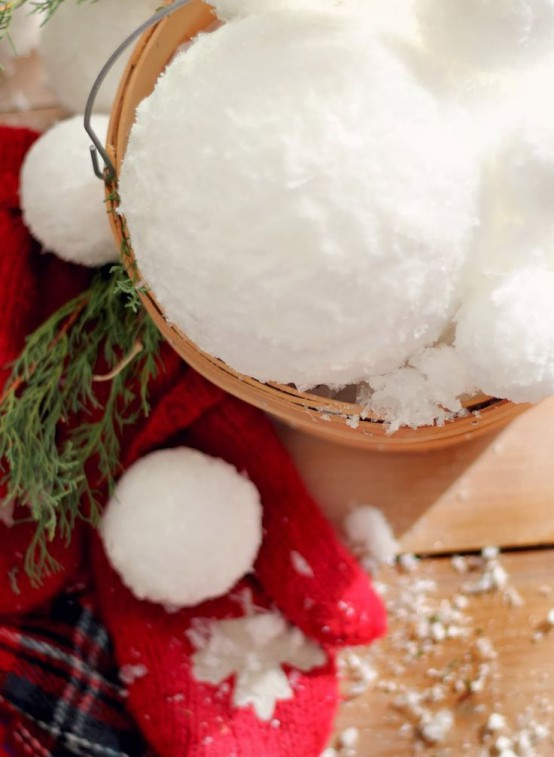 a wooden basket with snowballs is a cool decoration in rustic style and can be used both indoors and outdoors