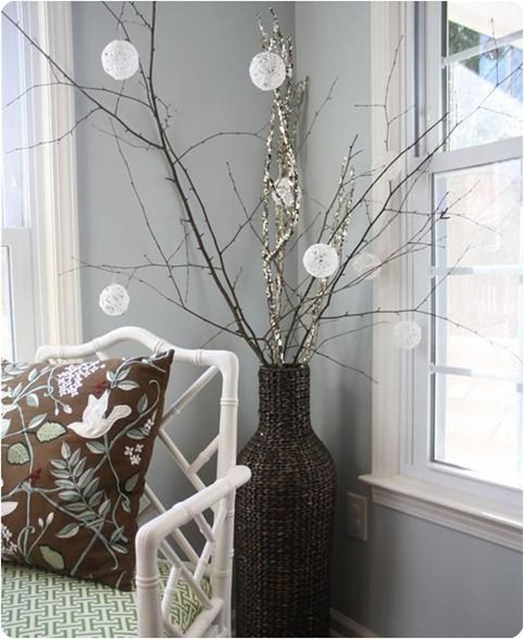 a woven vase with large branches, with lights and snowball ornaments is a pretty and chic decoration for indoors and outdoors