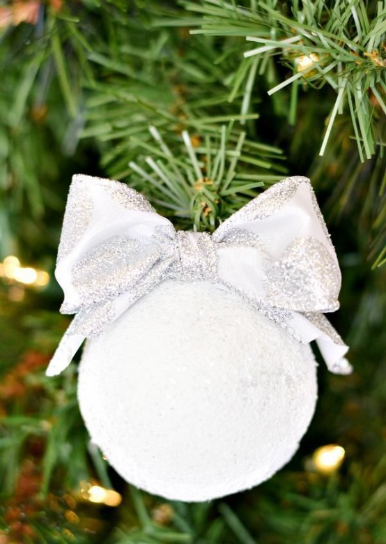 a snowball with a silver bow is a cool and cute Christmas ornament to rock