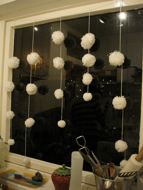 white pompoms hanging down as snowballs on the window will bring a strong winter feel indoors