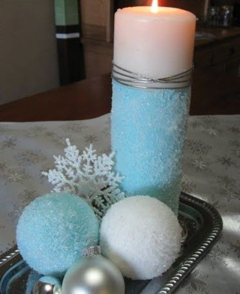 a simple winter or Christmas centerpiece of a tray with blue and usual snowballs, ornaments, snowflakes and a colored candle is lovely