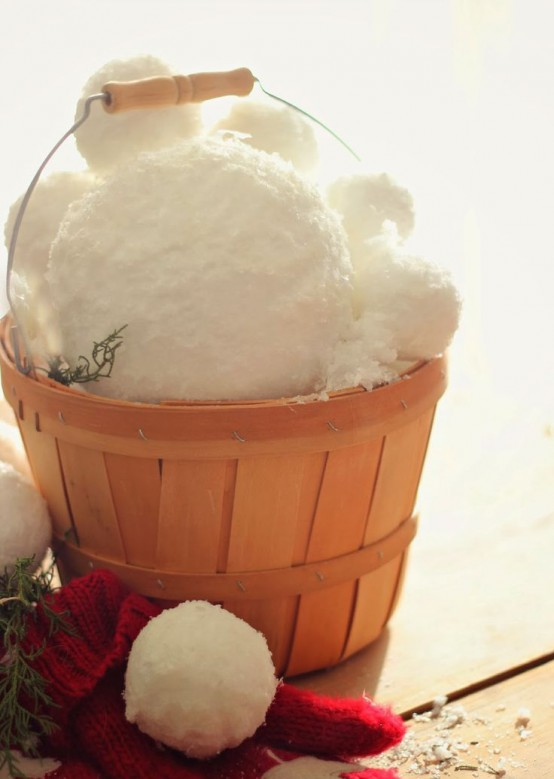 a wooden basket filled with large snowballs is a great idea for a rustic winter space, it can bring a cozy feel both indoors and outdoors