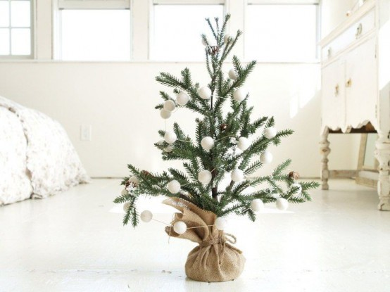 a Christmas tree in burlap, with white snowball ornaments is a pretty and simple winter decoration to rock