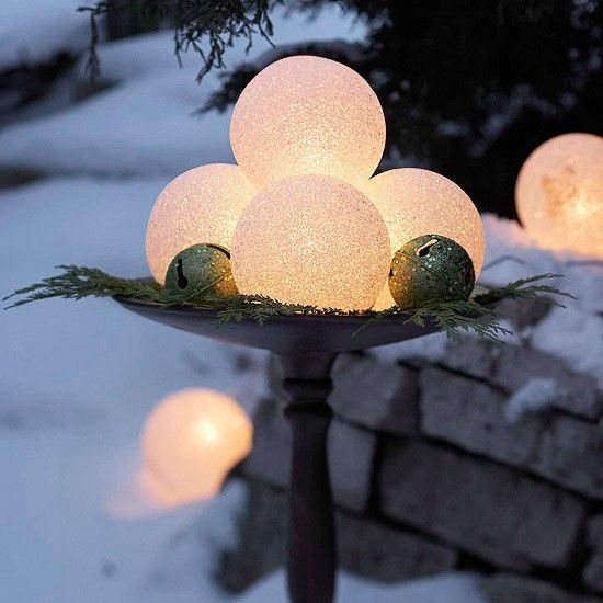 a metal bowl with lit up snowballs, bells and fir twigs is a lovely decoration for outdoors, it will bring some light