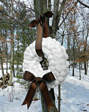 a large snowball wreath with a brown bow and a ribbon on top is a chic idea for winter