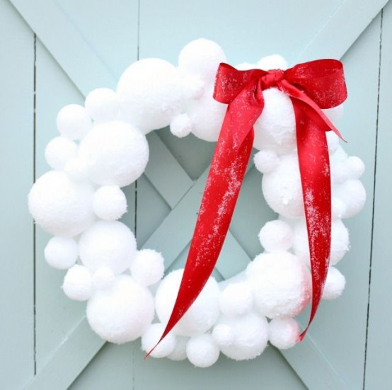 a snowball Christmas wreath accented with a large red bow will bring a snowy and fairy-tale feel to the space