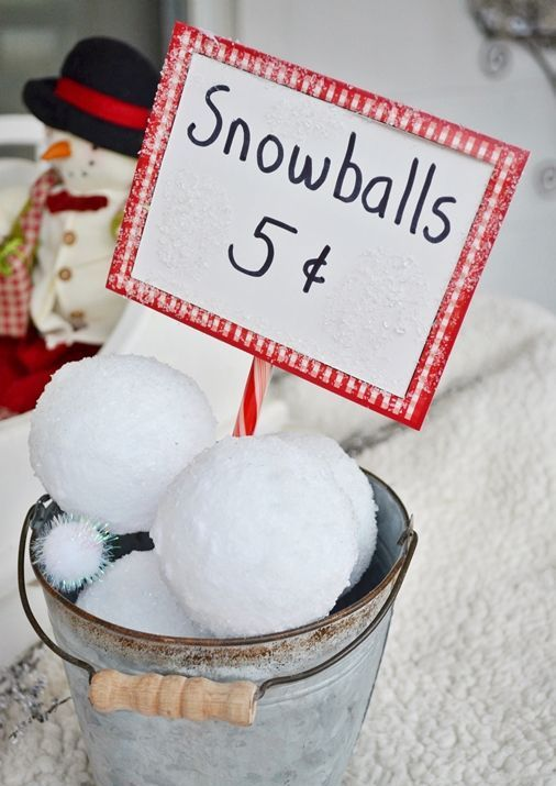 a bucket with large snowballs and a sign is a cool rustic decoration for both indoors and outdoors