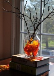 a sheer glass vase with fall leaves, branches and twigs is a simple last minute decoration for the fall