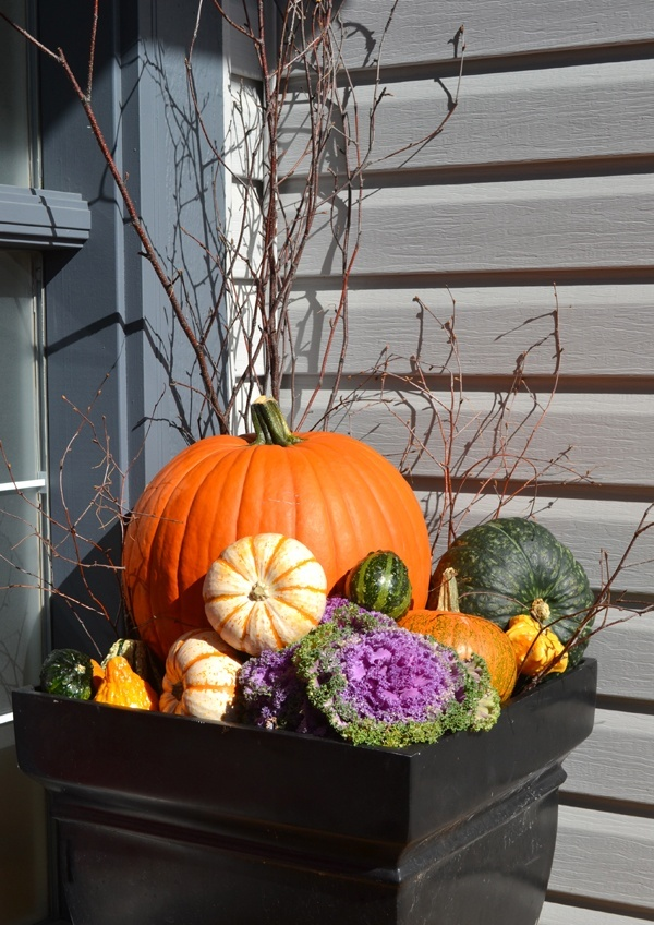 a natural outdoor fall arrangement of a large planter with pumpkins, gourds, blooms, cabbage and twigs and branches