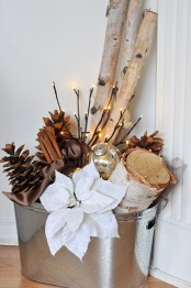 a fall to winter rustic arrangement with pinecones, cinnamon, tree stumps and branches, lights and white fabric blooms