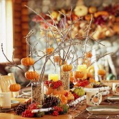 tall glasses with grain, twigs and branches with pumpkins, pinecones, faux gourds and veggies and berries compose a chic fall centerpiece