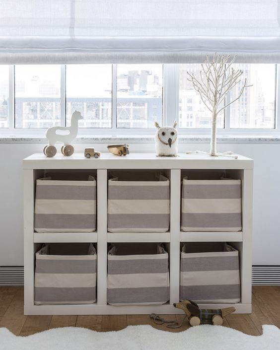 an open storage unit with fabric boxes that work as drawers give the nursery a neat look
