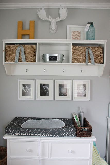 an open storage shelf with baskets and some hooks to store some stuff over the changing table