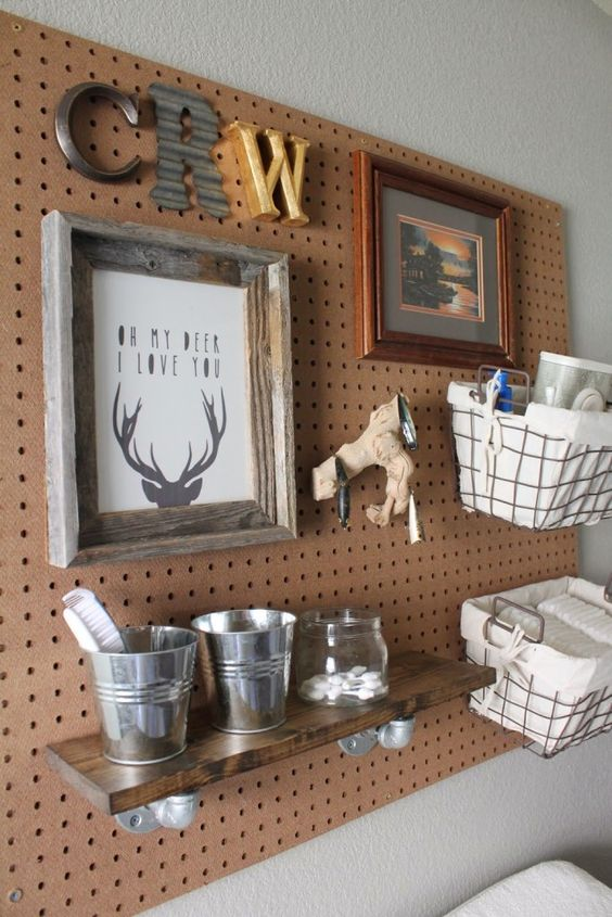 a pegboard with wire baskets, a shelf and even some art is a cool piece to hang over the changing table