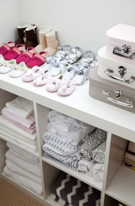 a large open storage unit in white and several vintage suitcases are a stylish option to organize a girl's closet
