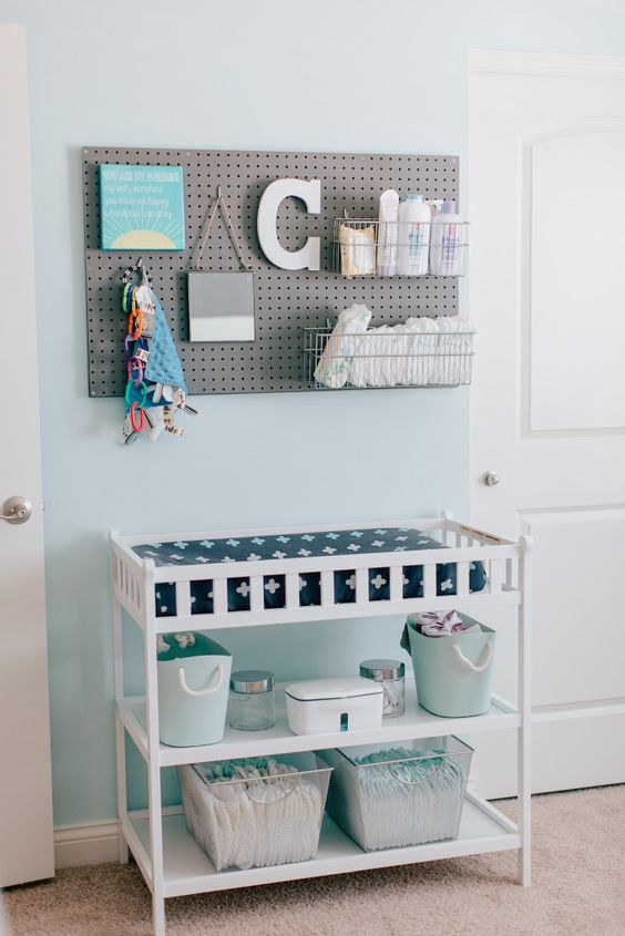 a pegboard with wire baskets and a changing table with open storage spaces