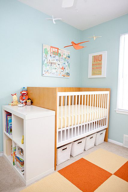 boxes inserted under the bed and a shelving unit next to it to store and organize stuff in your nursery