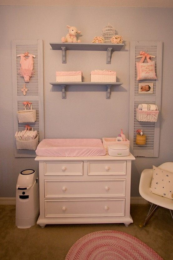 A Changing Table With Some Shelves Over It Shutters Baskets Hanging On Them