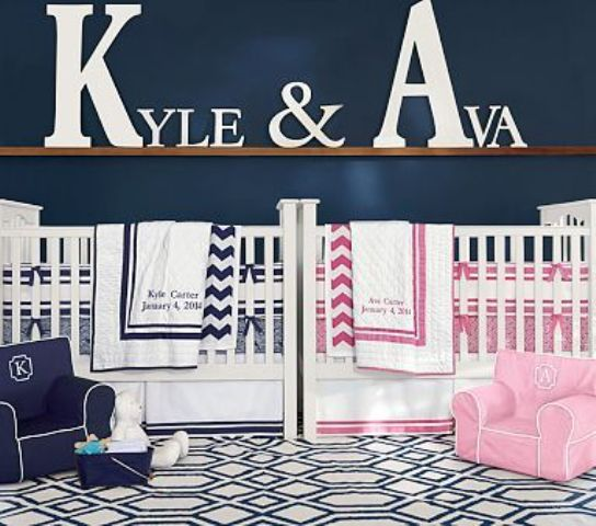 a blue and white shared nursery with navy, pink and white bedding and the names of the kids on the ledge