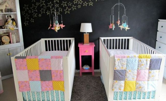 a stylish shared nursery with a chalkboard wall, stars chalked on it, white furniture and colorful patchwork bedding plus colorful mobiles