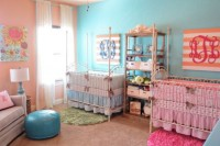 a colorful nursery with an accent pink and blue wall, with neutral furniture and a blue ottoman and various printed bright bedding