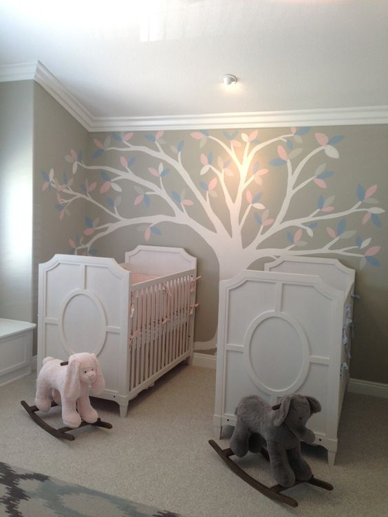 a neutral shared nursery with white furniture, a tree painted on the wall and some toys