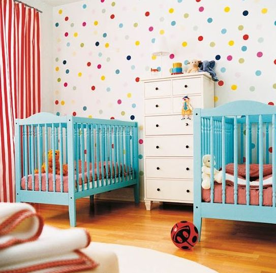 a colorful shared nursery with a bright polka dot wall, turquoise cribes, pink and white bedding and lots of toys