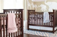 a neutral nursery in tan and white, with stained wooden cribs, with blue and pink printed linens is stylish and cute