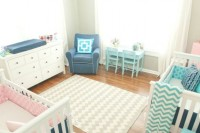 a neutral shared nursery with white and blue furniture and printed pink and blue linens plus a printed rug