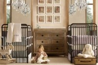 a neutral rustic nursery with dark forged beds, a wooden dresser, a gallery wall, crystal chandeliers and neutral toys
