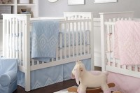 a grey and white shared nursery with white furniture, white monograms and artworks and pink and blue bedding