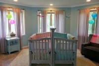 a colorful shared nursery with bright linens and lamps, with grey and blue furniture for fun