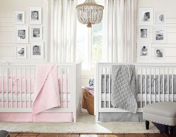 a neutral shared nursery with white walls and furniture, a beaded chandelier, photos and grey and pink bedding