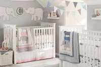 a neutral shared nursery with grey walls, white furniture, paper buntings and decorations, blue and pink bedding to accent each space