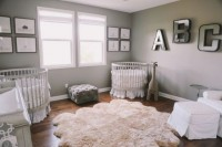 a gender neutral shared nursery with grey walls, white furniture, two gallery walls, matching cribs and monograms on the wall