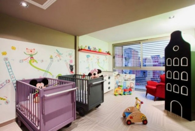 a colorful shared nursery with bright images on the wall, lots of toys and matching colorful beds is a fun idea
